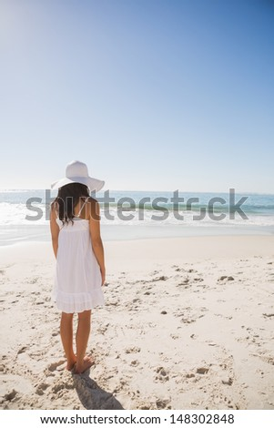 Brunette in white sunhat and dress looking at the ocean at the beach