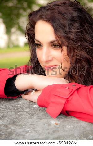 Brunette is leaning against a stone - stock photo