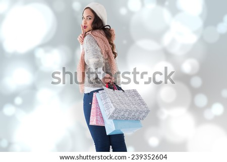 Brunette keeping a secret and holding shopping bags against blurred lights - stock photo