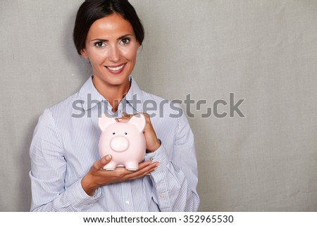 Brunette lady holding porcelain piggy bank while looking at camera in formal clothing on grey texture background