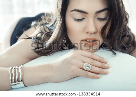 Brunette lady with jewelry laying on the bed
