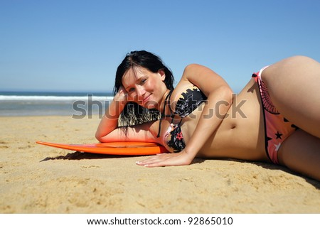 Brunette laying seductively on surfboard - stock photo