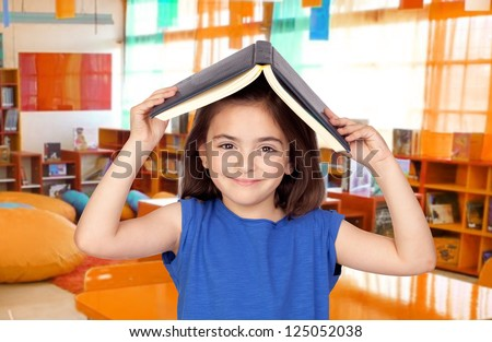 Brunette little girl with a book on her head in the class - stock photo