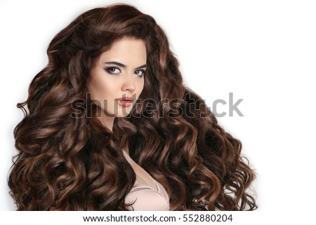 Brunette. Long hair. Curly hairstyle. Beautiful woman with wavy healthy hair isolated on studio white background. Beauty makeup. Shampoo healthcare. Stare.
