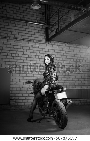 Brunette long-hair girl in a stockings and leather jacket on sport bike.