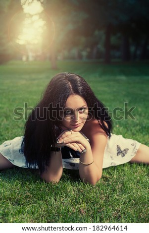 Brunette lying on green grass and looking at camera
