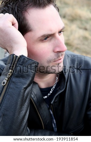Brunette male model against a brick wall background - stock photo
