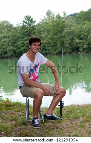 Brunette Man Fishing at a lake with green water - stock photo