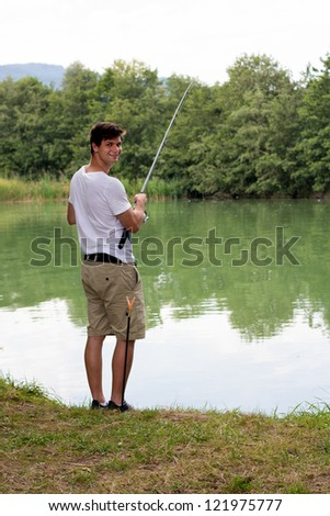 Brunette Man Fishing at a lake with green water