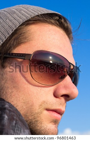 Brunette Man With Sunglasses And A Hat Looking Into The Blue Sky