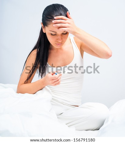brunette measures the temperature of a sick in bed