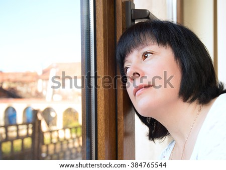 Brunette middle-aged woman is looking out the window - stock photo
