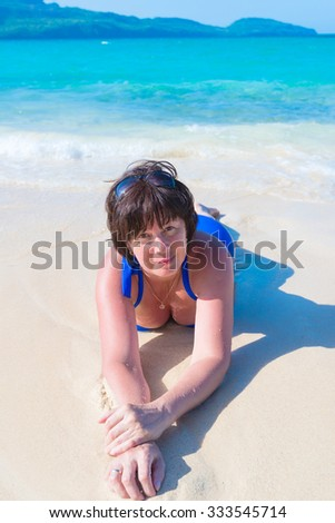 brunette middle-aged woman lying in the sea on a white sand beach