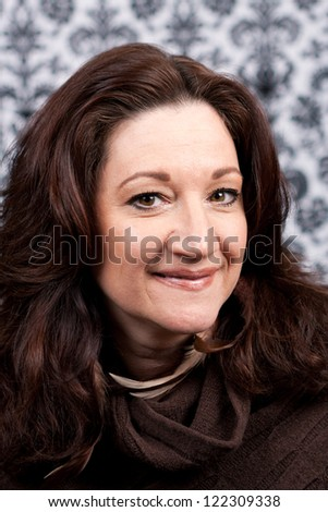 Brunette middle aged woman with feather hair extensions and accessories. - stock photo