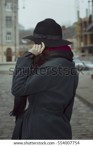 Brunette model in hat and coat at the street in Lviv
