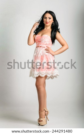 Brunette model posing in cute pastel cocktail dress - stock photo