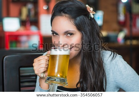 Brunette model sitting by restaurant table drinking from glass of beer and posing with positive attitude smiling.