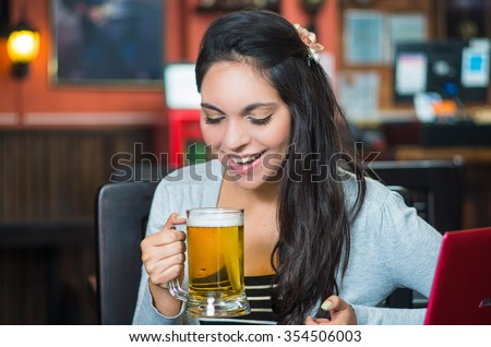 Brunette model sitting by restaurant table holding glass of beer and posing with positive attitude smiling.
