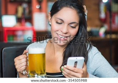 Brunette model sitting by restaurant table holding glass of beer and using mobile phone while smiling.