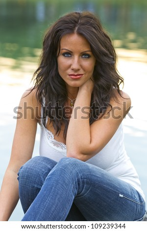 Brunette model sitting in a park near a pond - stock photo
