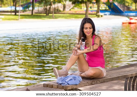 Brunette model wearing pink top and white shorts relaxing in park environment, sitting on bench next to lake using insect repellent spray.