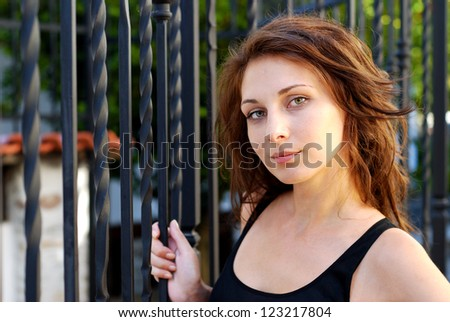 Brunette next to a metal fence - stock photo