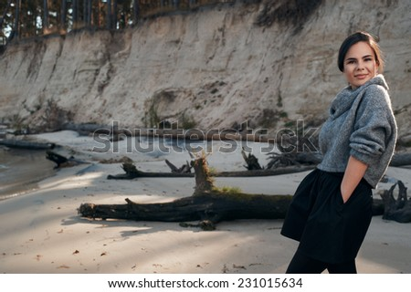 brunette on sea coast in autumn wearing grey pullover