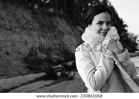 brunette on seashore wearing coat, monochrome image - stock photo