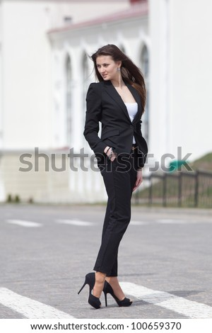 Brunette on stiletto heels outdoors. Young woman in black suit walking along the crosswalk - stock photo