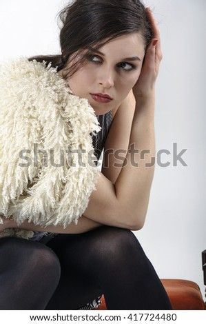 Brunette posing in the studio for a fashion catalog against a white background