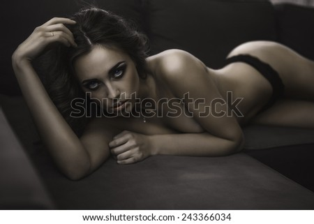 brunette posing topless on a bed in a hotel - stock photo