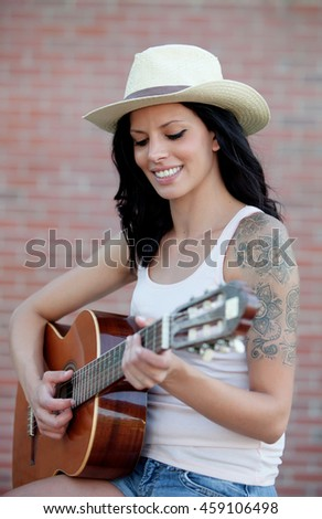 Brunette pretty woman playing a clasic guitar  - stock photo