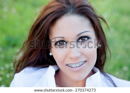 Brunette pretty woman with brackets relaxing in the park