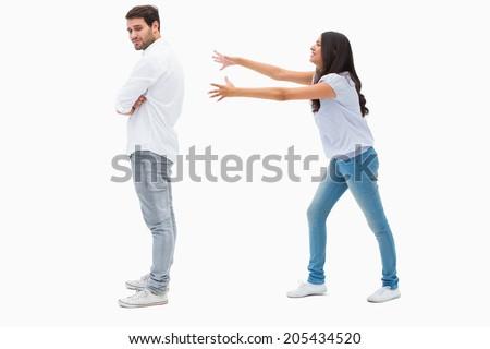Brunette reaching desperately for man on white background - stock photo