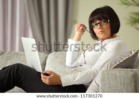brunette relaxing on sofa with laptop