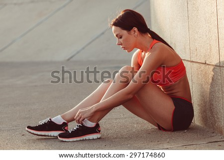 brunette runner woman sitting on the ground and tie laces, sunset time, evening workout