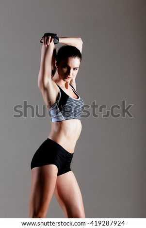 Brunette sexy fitness girl in sport wear with perfect body in the gym posing before training set.  - stock photo