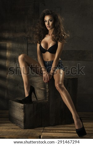 Brunette sexy woman sitting on wooden pallets  - stock photo