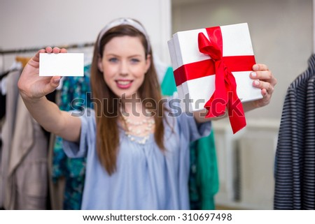 Brunette showing gift and card to camera in fashion boutique - stock photo