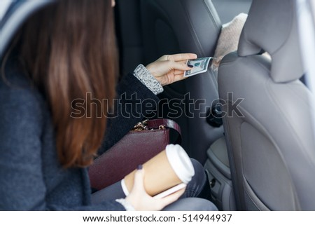 Brunette sitting in taxi transfers money for travel