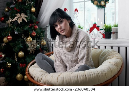 brunette sitting in the armchair in christmas eve - stock photo