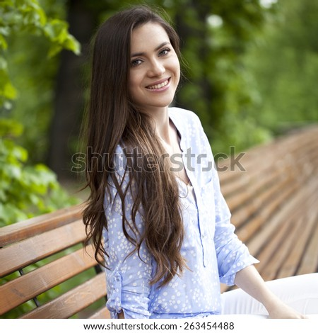 Brunette sitting on a bench in a summer park - stock photo