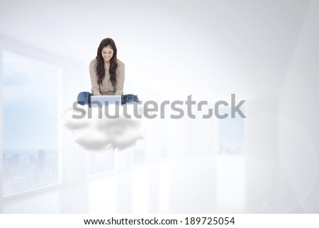 Brunette sitting on cloud using laptop against bright white hall with columns - stock photo
