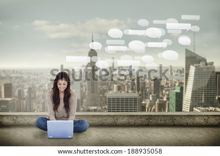 Brunette sitting on floor using laptop against balcony overlooking city - stock photo