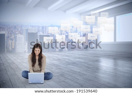 Brunette sitting on floor using laptop against city scene in a room - stock photo