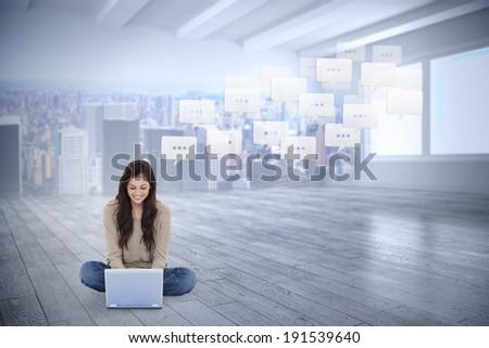 Brunette sitting on floor using laptop against city scene in a room - stock photo