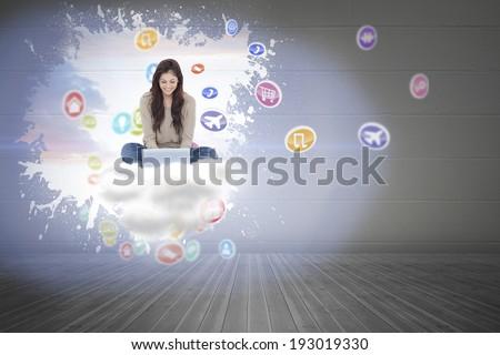 Brunette sitting on floor using laptop against splash on wall revealing bright sky - stock photo