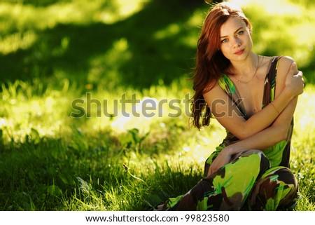 brunette sitting on green grass - stock photo