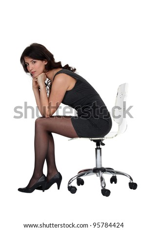 Brunette sitting on office chair - stock photo
