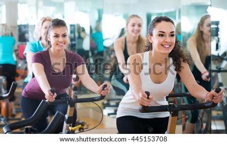 Brunette smiling spanish girl and other females working out in sport club